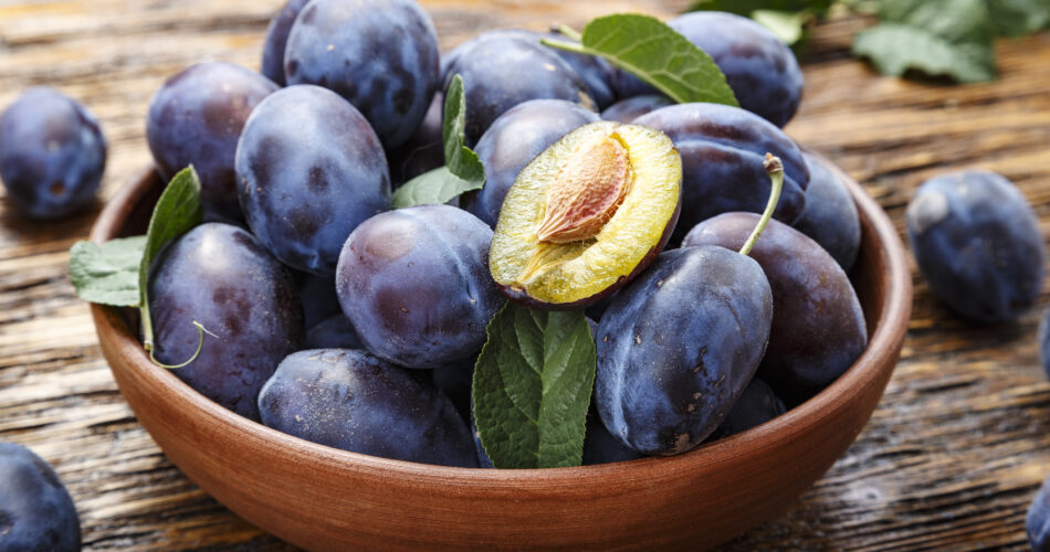 raw plums in a plate on a brown wooden background. place for text