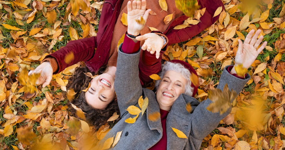 Senior grandmother and smiling granddaughter lying on yellow and red leaves at park, view from above. Top view of playful old woman with cheerful girl lying on autumn park leaves. High angle view of happy grandmother and young woman playing with dried leaves while lying on ground at park and looking at camera.